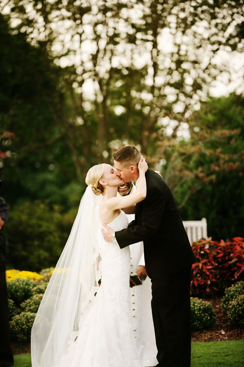 first kiss at an outdoor dallas arboretum wedding image